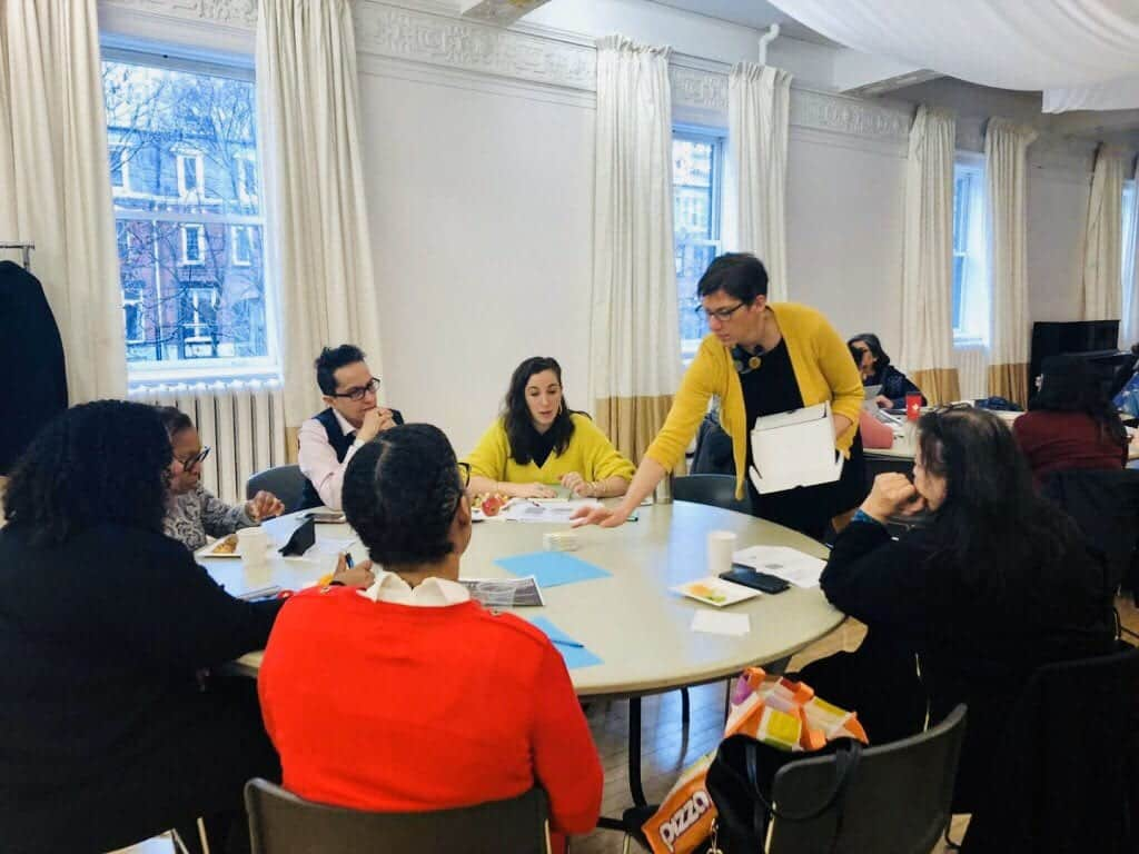 a group of people working together at a table with a facilitator handing out papers